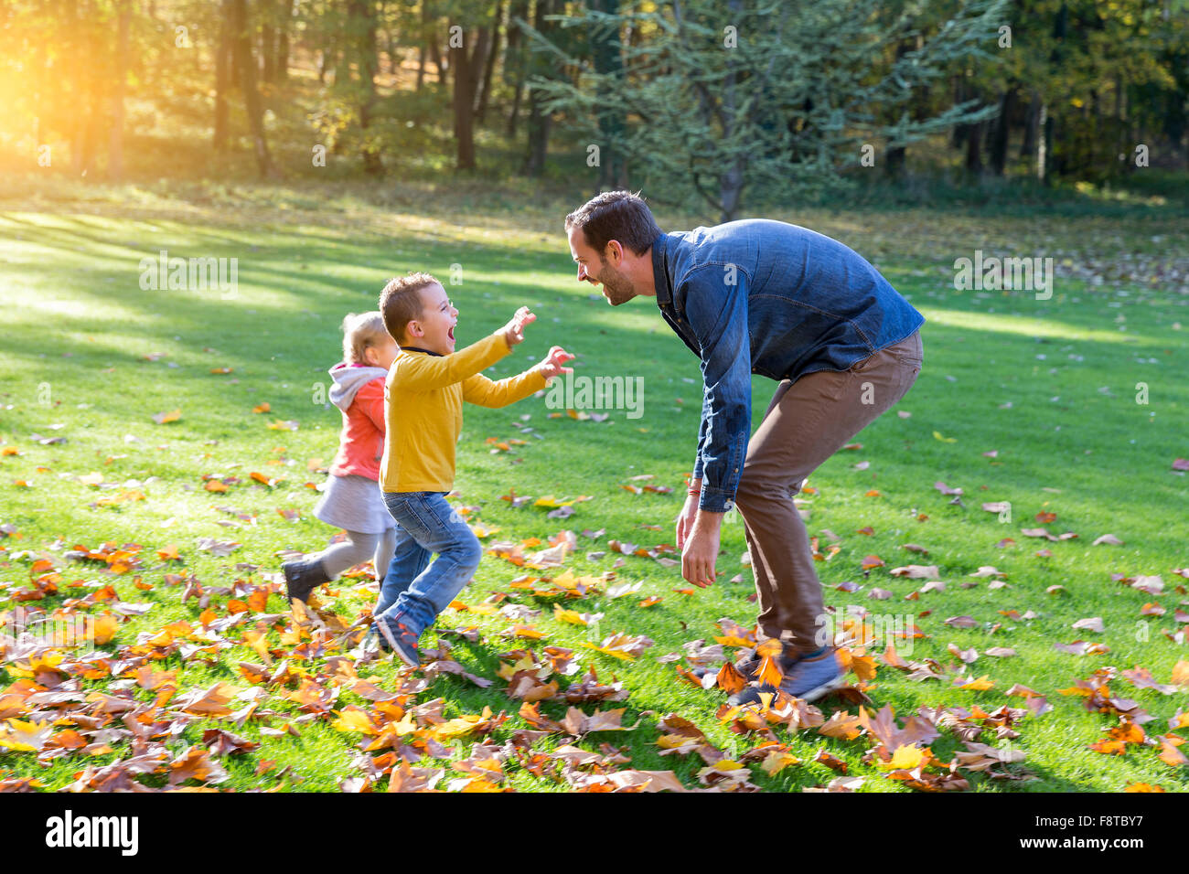 Father with his children playing in park - Stock Image