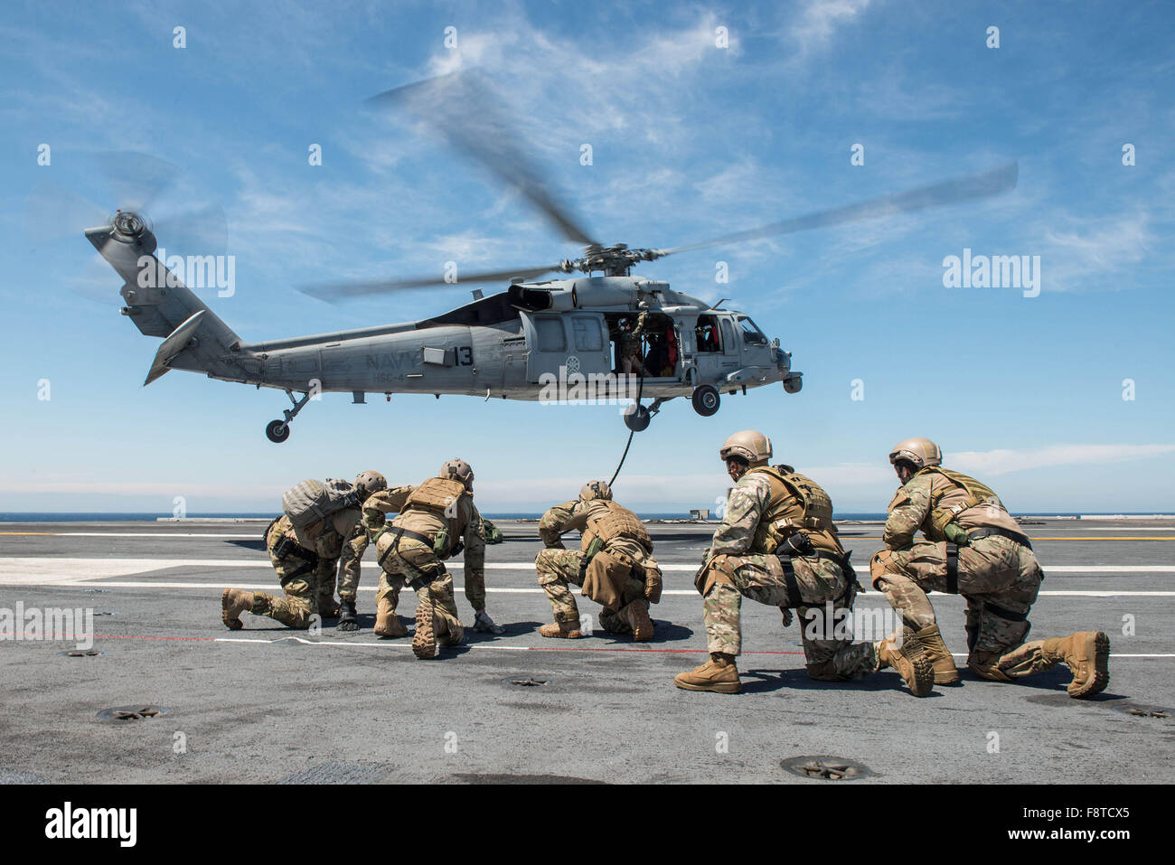 Sailors assigned to Explosive Ordnance Disposal Mobile Unit (EODMU) 3, Platoon 3-1-1 and Chilean navy sailors brace - Stock Image