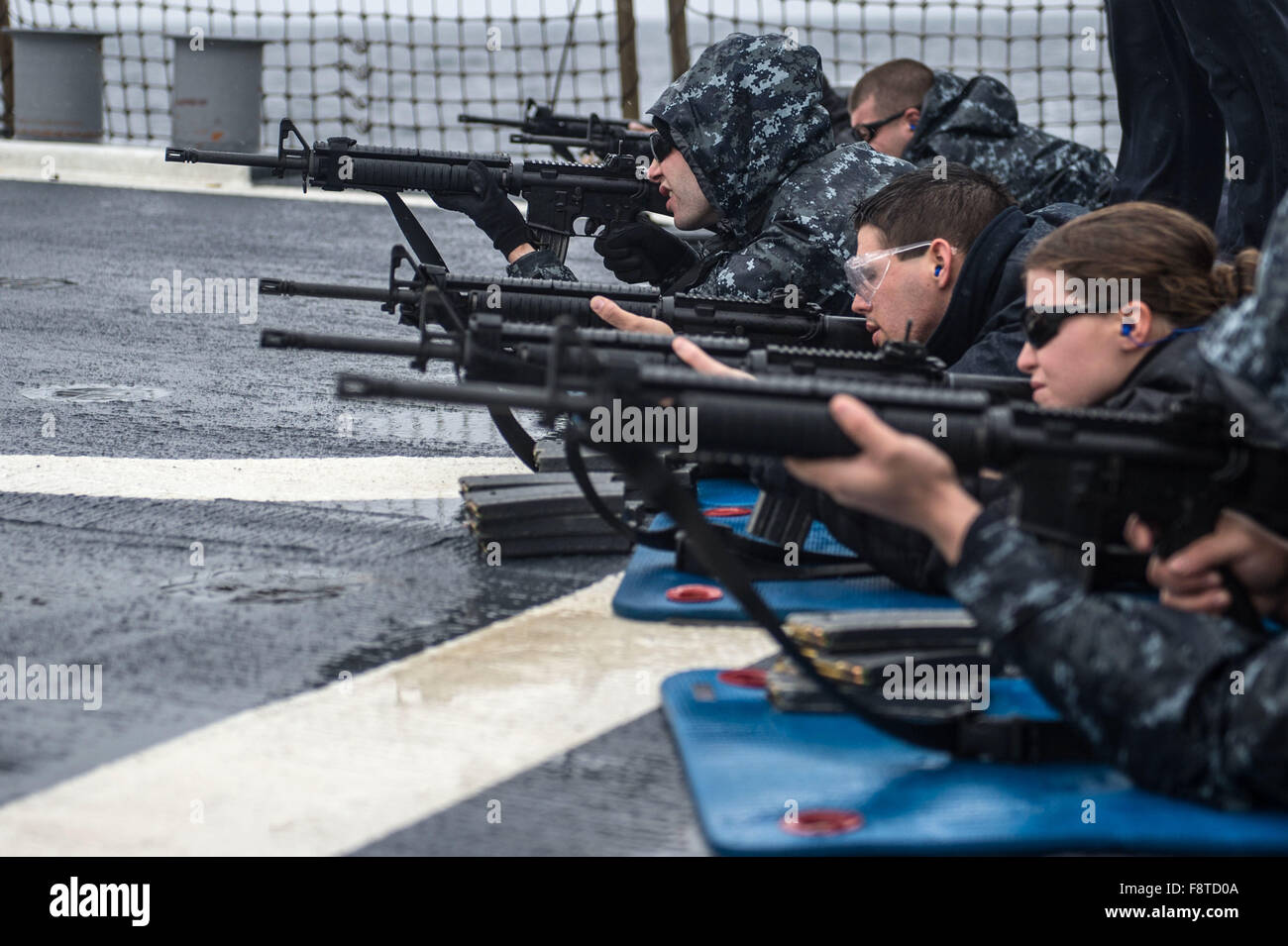 Sailors participate in a M16 live-fire exercise on the flight deck of the forward-deployed Arleigh Burke-class guided Stock Photo