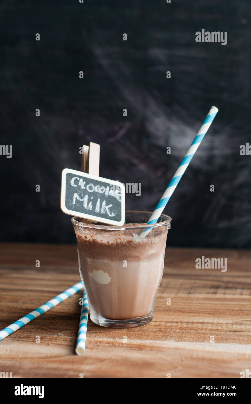 Chocolate Milkshake on a wooden background with paper straw and chalkboard clips with text written and against chalkboard - Stock Image