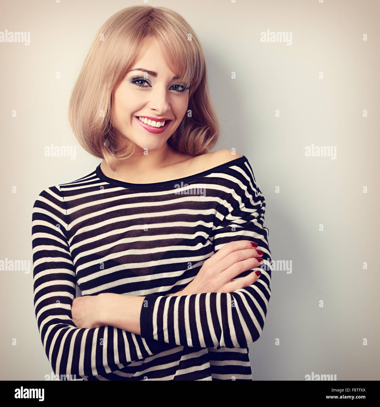 Beautiful happy casual blond woman with folded arms looking with smiling. Toned portrait - Stock Image