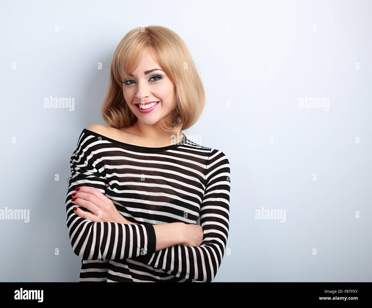 Beautiful happy casual blond woman with folded arms looking with smiling on blue background - Stock Image