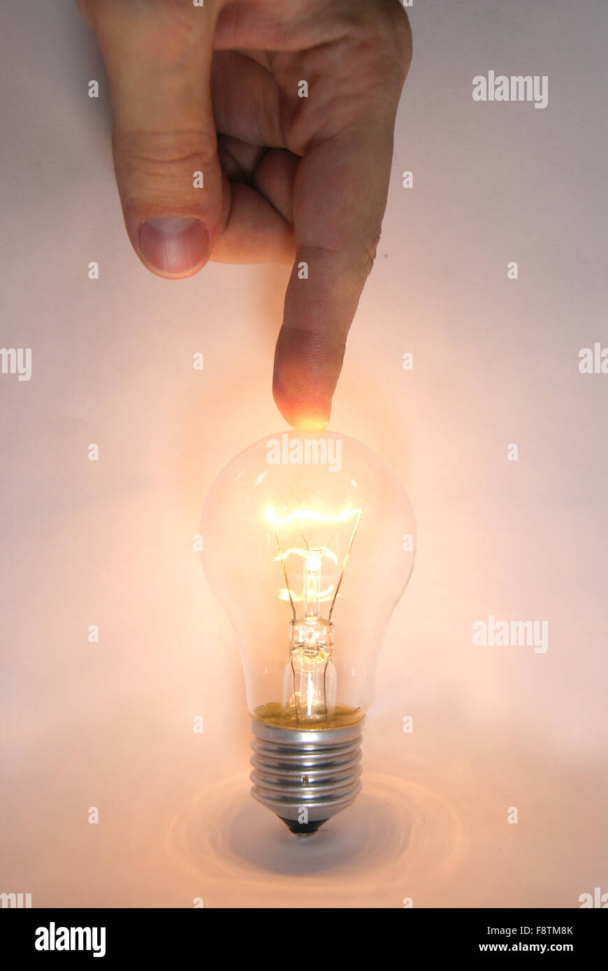 Human hand points a finger at the lamp on white background new idea - Stock Image