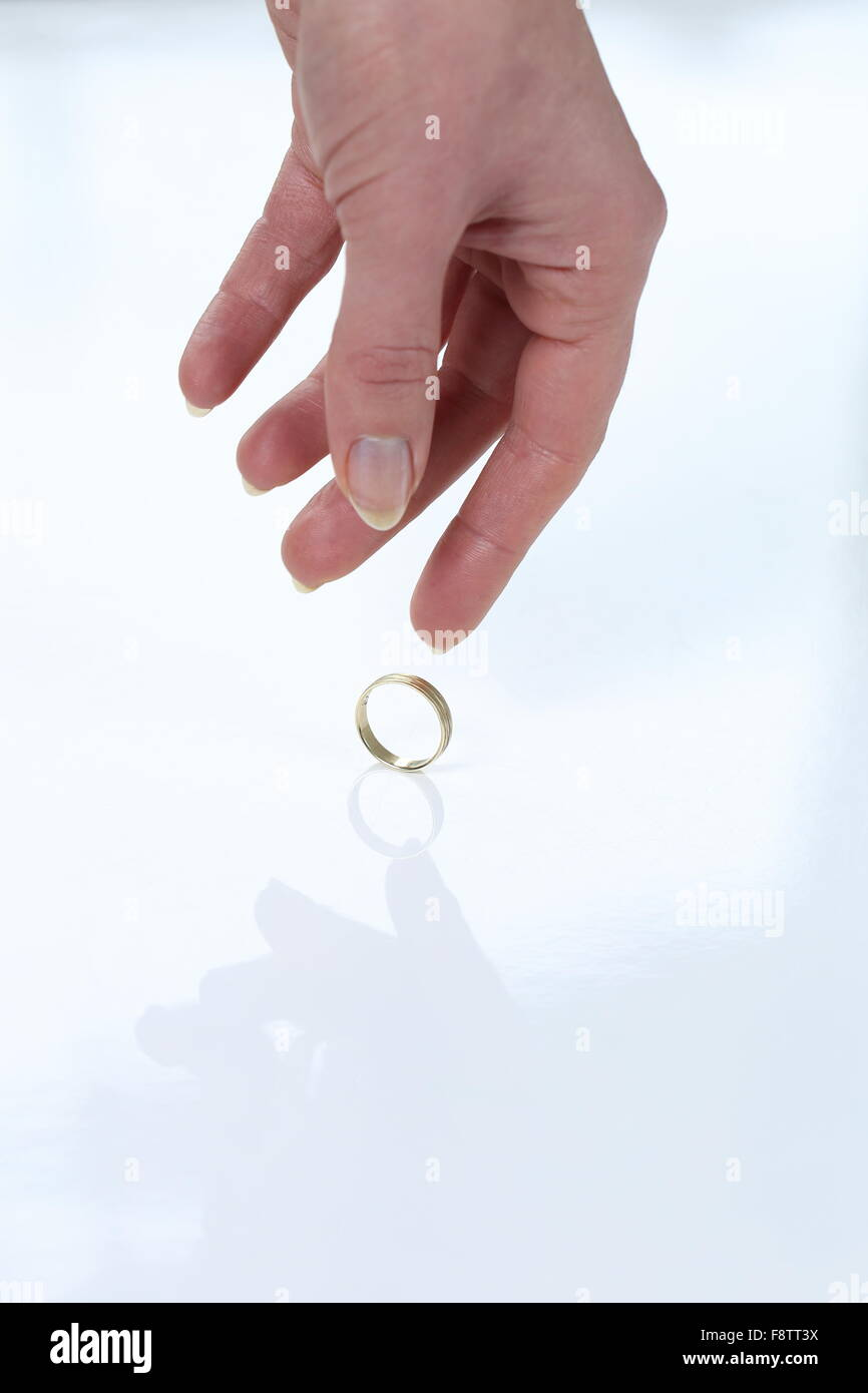 A Woman placing wedding ring on a table leaving her husband - Stock Image