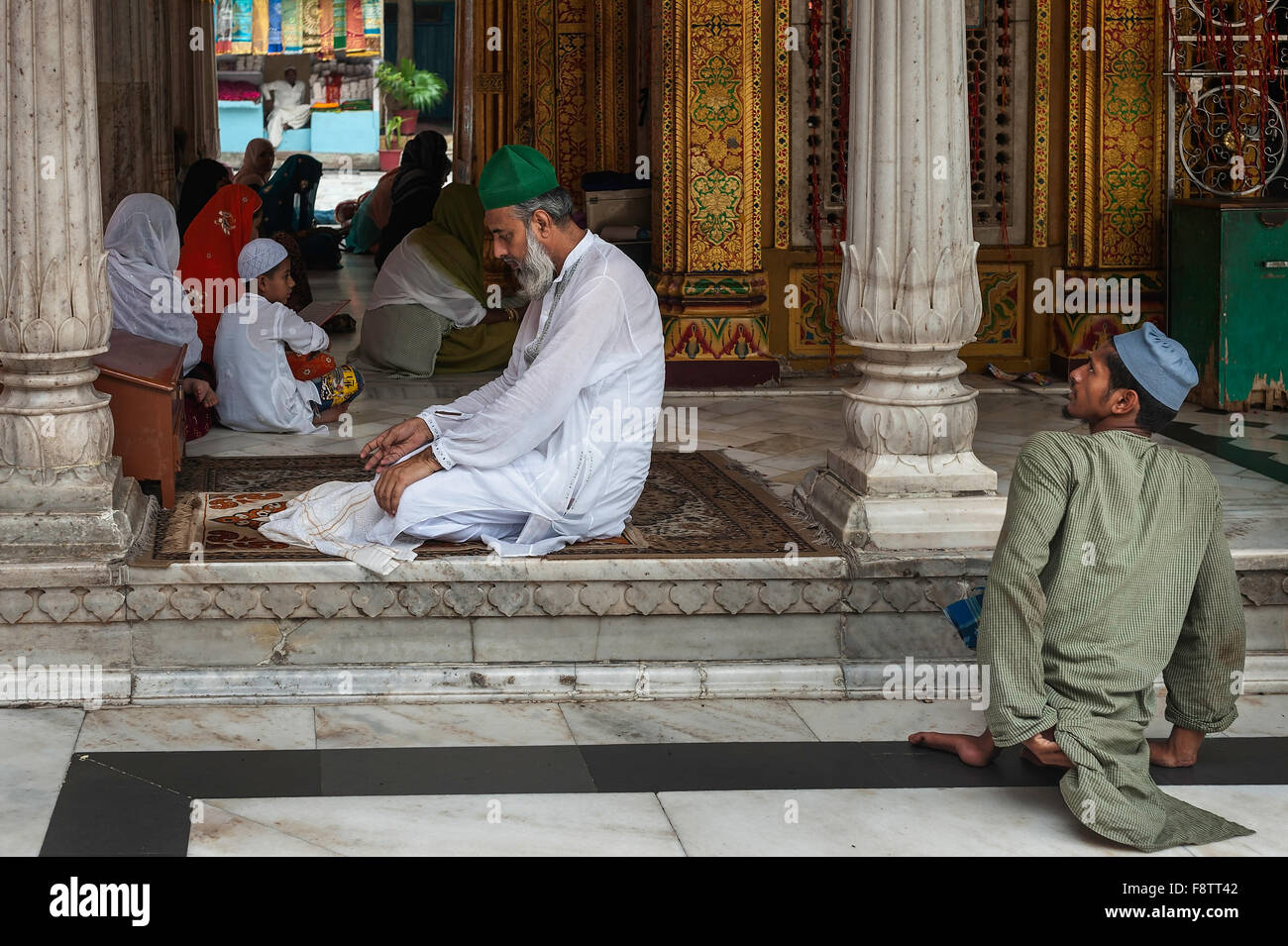 Disabled beggar waits patiently for a potential patron to finish his prayers at the beautiful mosque, Nizamuddin, - Stock Image