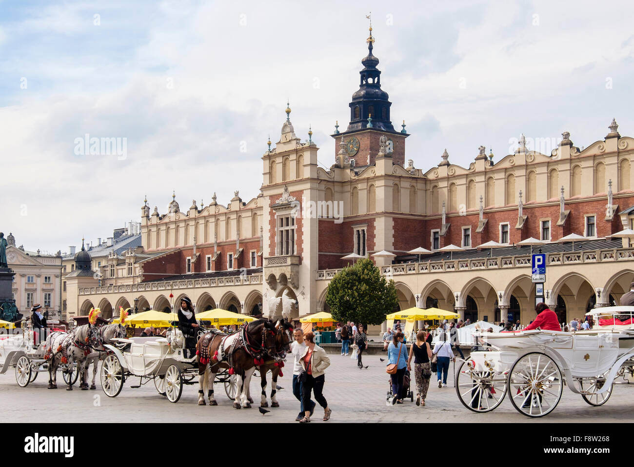 City tour horse-drawn carriages outside 13th century Sukiennice (Cloth Hall or Drapers' Hall) in Market Square - Stock Image