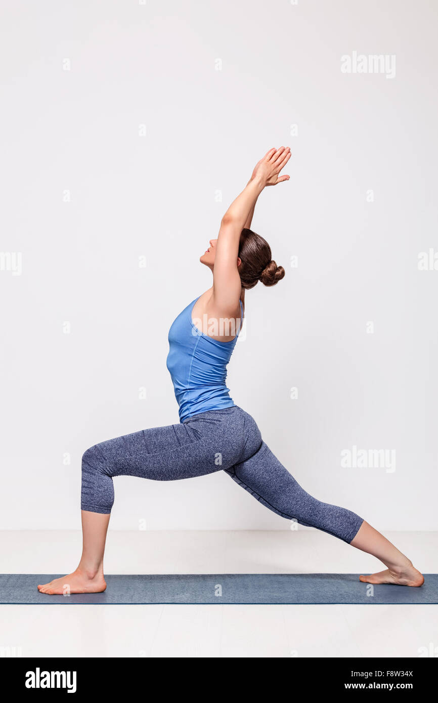 Sporty woman practices yoga Warrior pose asana - Stock Image