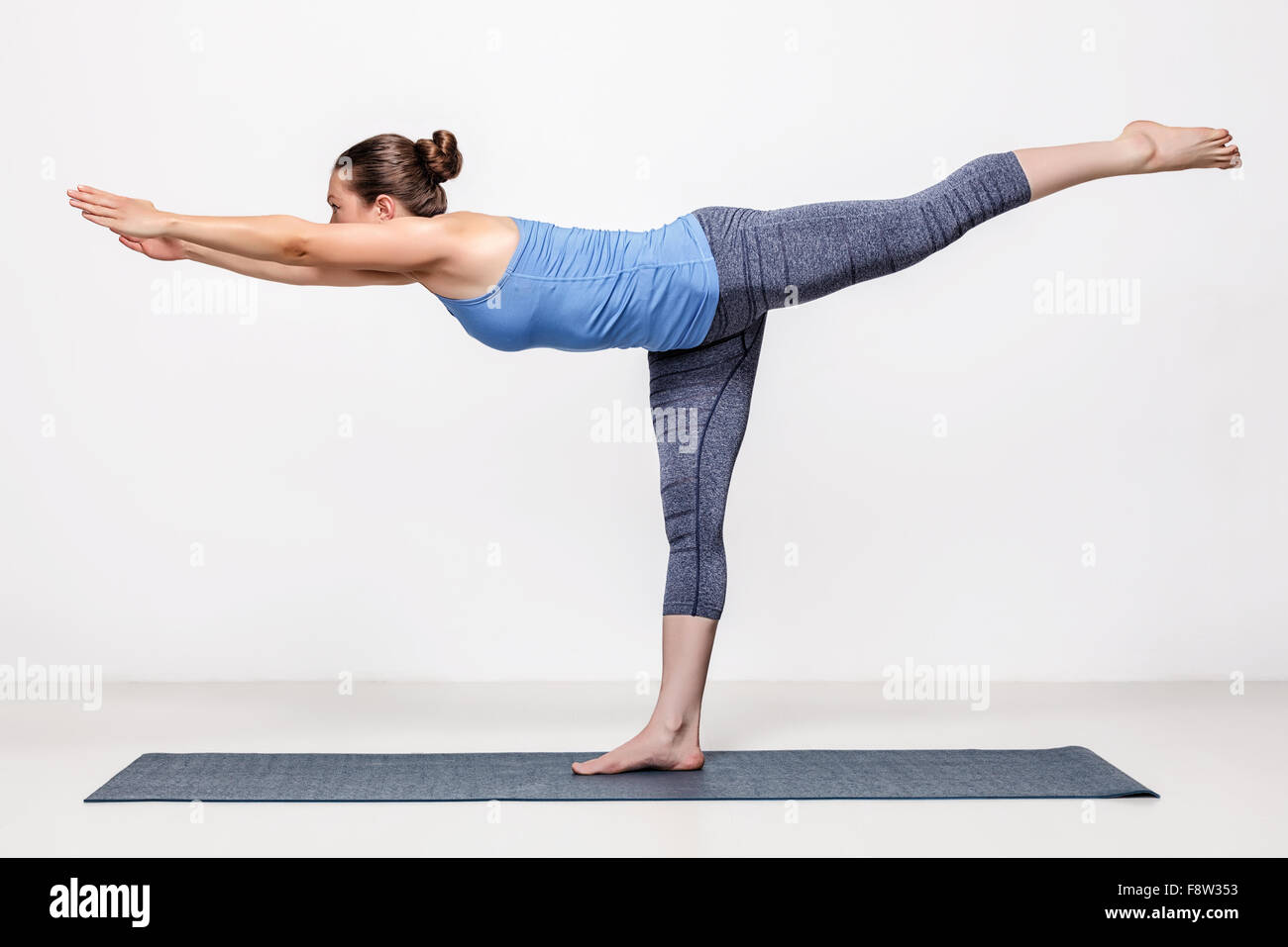 Sporty woman practices yoga asana - Stock Image