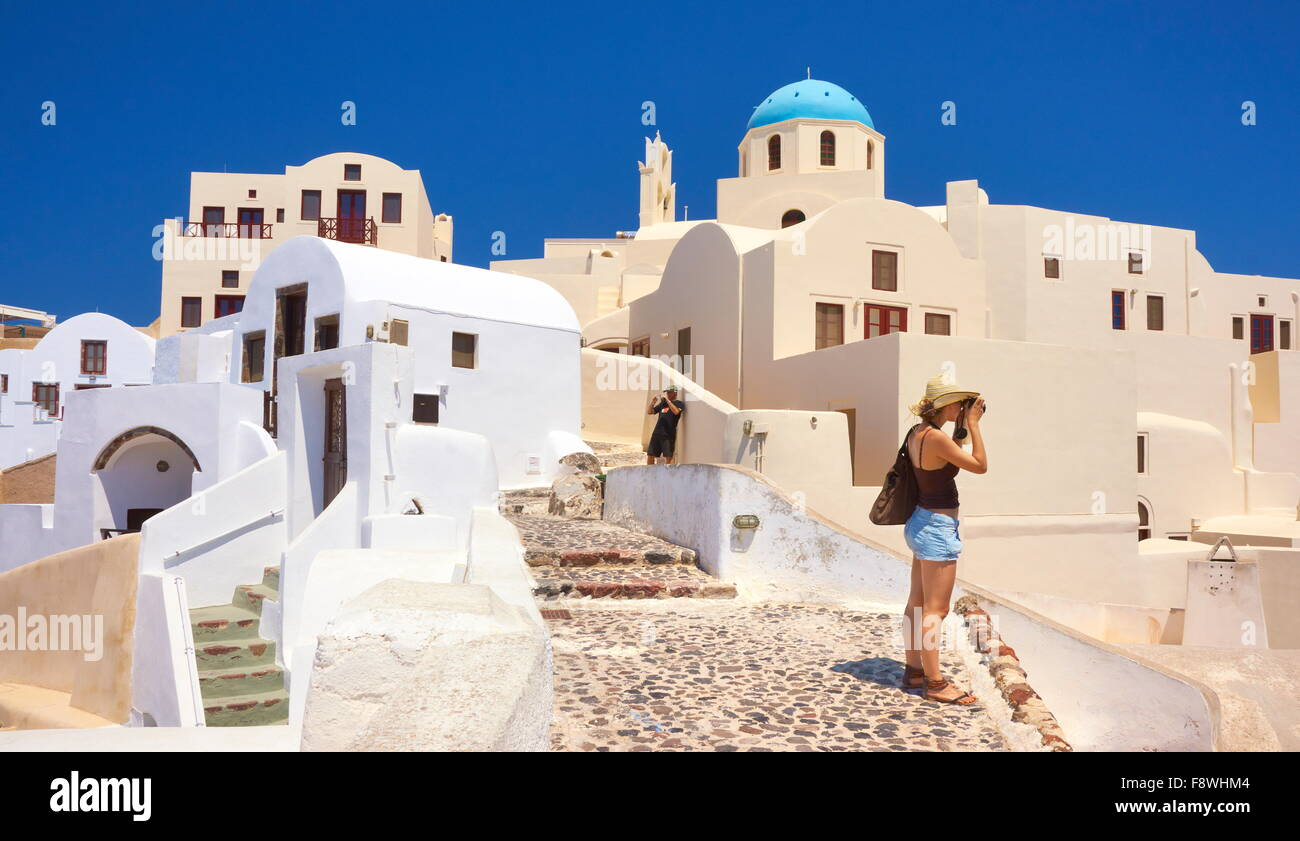 Santorini Caldera, Greece - tourist takes pictures of Oia houses, Cyclades Islands, Greece - Stock Image