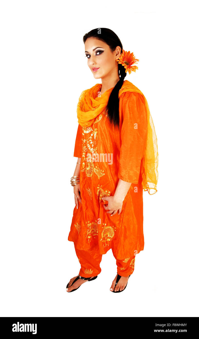 7bec44e360 A very pretty east indian teenage girl standing in her traditional indian  dress with a flower in her long black hair for white b