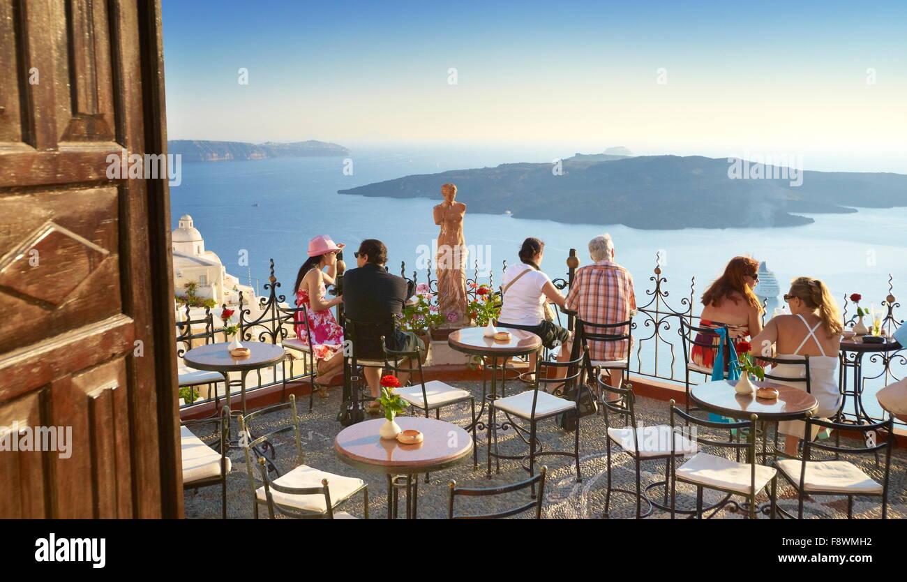 Thira (capital of Santorini) - tourists resting on the greek cafe restaurant terrace, Santorini Island, Greece - Stock Image