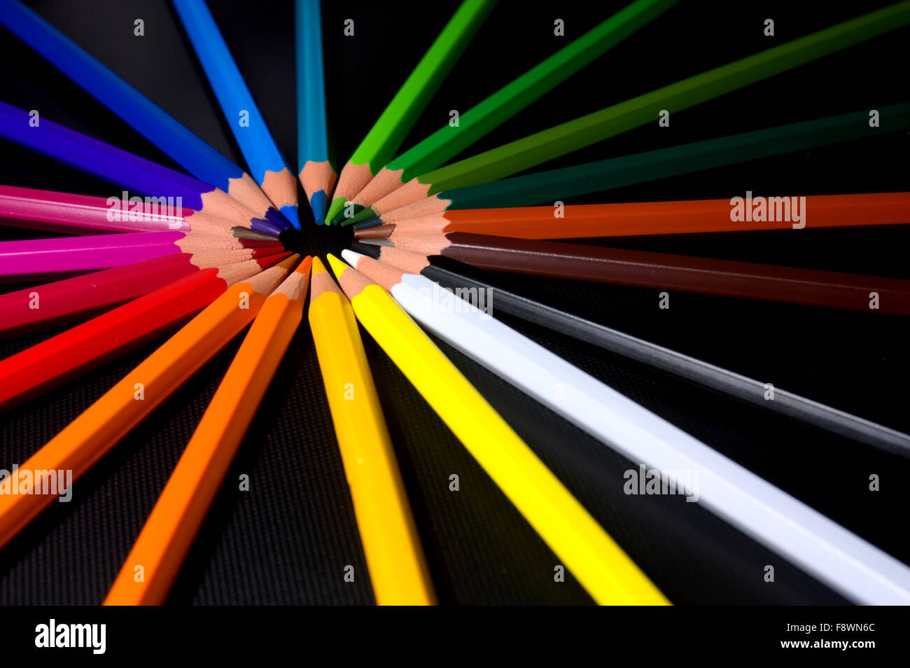 Brightly colored pencil crayons from the red side of the colour spectrum are arranged into a circle or wheel making - Stock Image