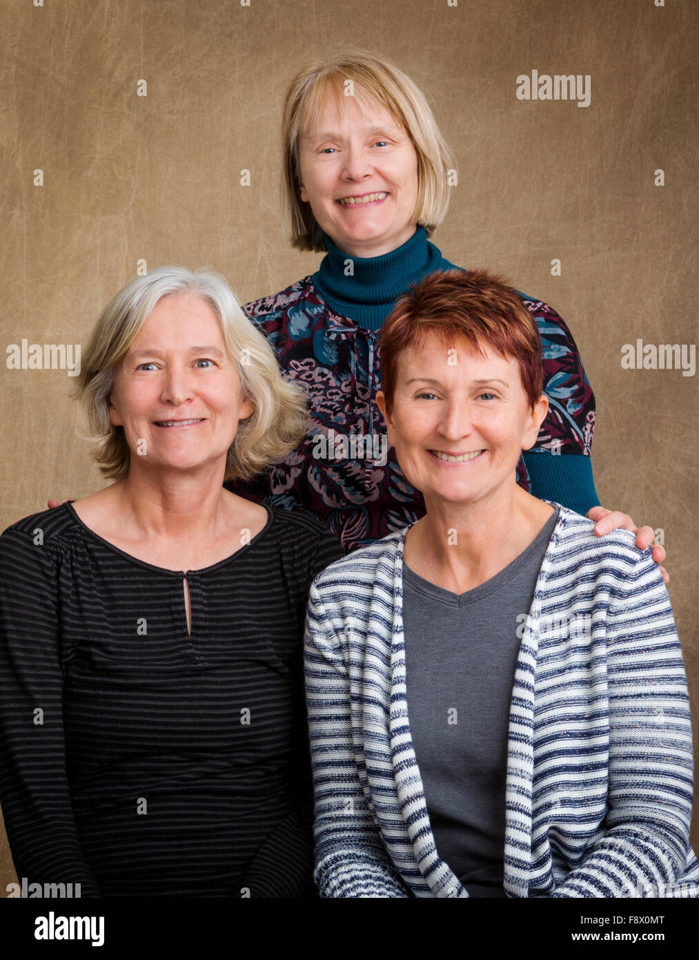 Studio photograph of three middle-aged female sisters - Stock Image