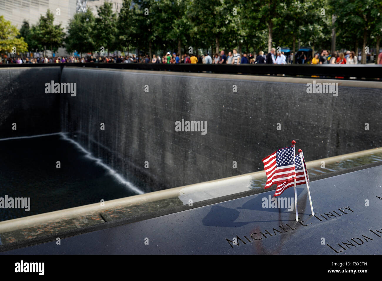 US flags placed on the name of a victim of terrorist attack on the National 9/11 Memorial, New York City, USA Stock Photo