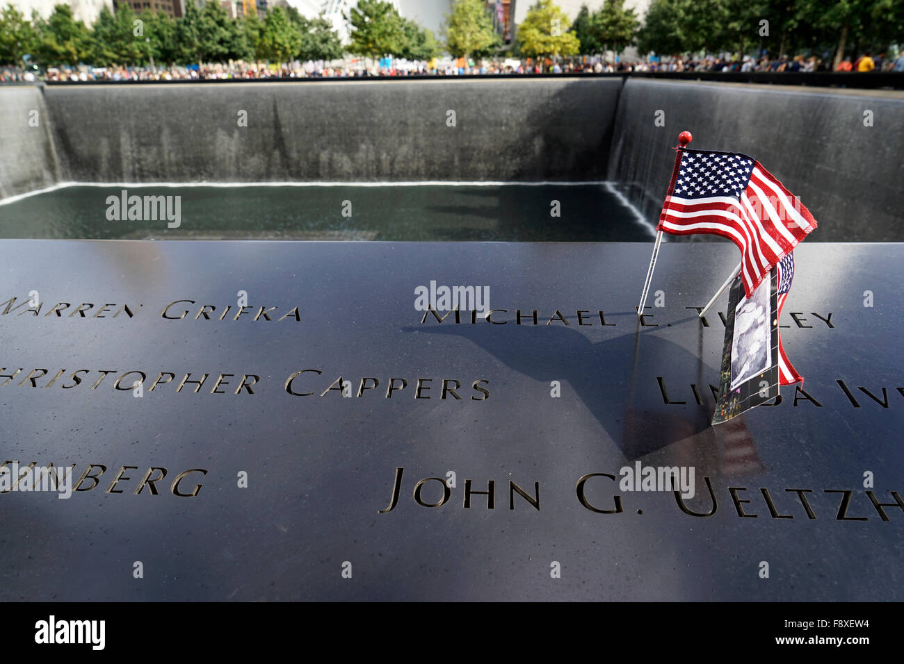 US flag and photography placed on the name of a victim of terrorist attack on the National 9/11 Memorial, New York - Stock Image