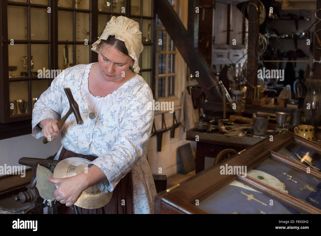 Williamsburg, Virginia - A costumed living history artisan works in the silversmith shop at Colonial Williamsburg. - Stock Image