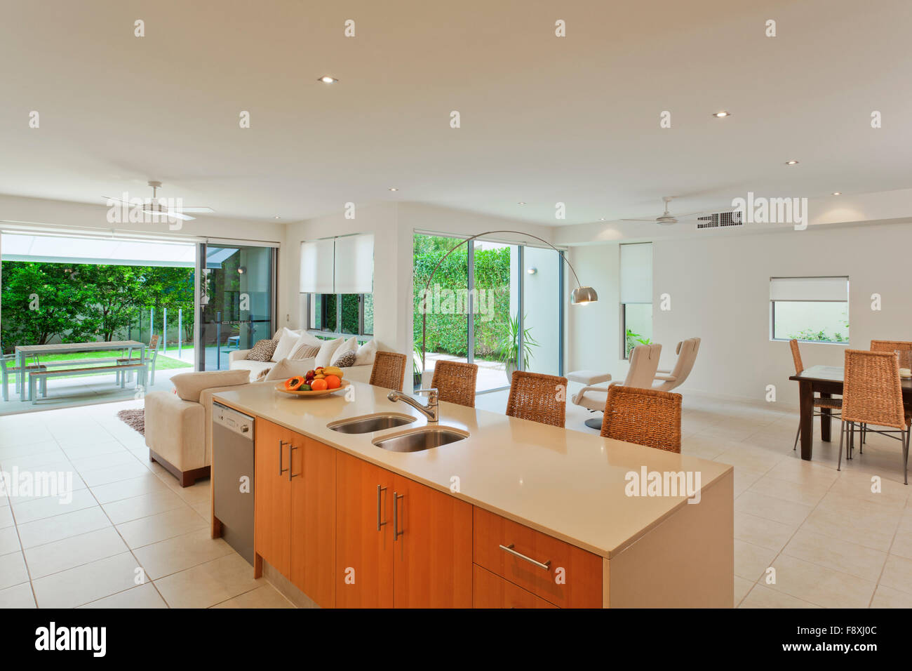 Luxurious modern kitchen and living room overlooking the backyard ...