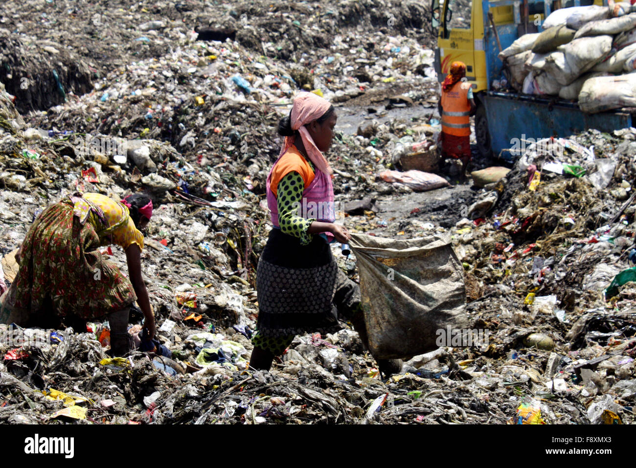 Child waste pickers pick the non- biodegradable waste to be used for the recycling industry. They are works in waste - Stock Image