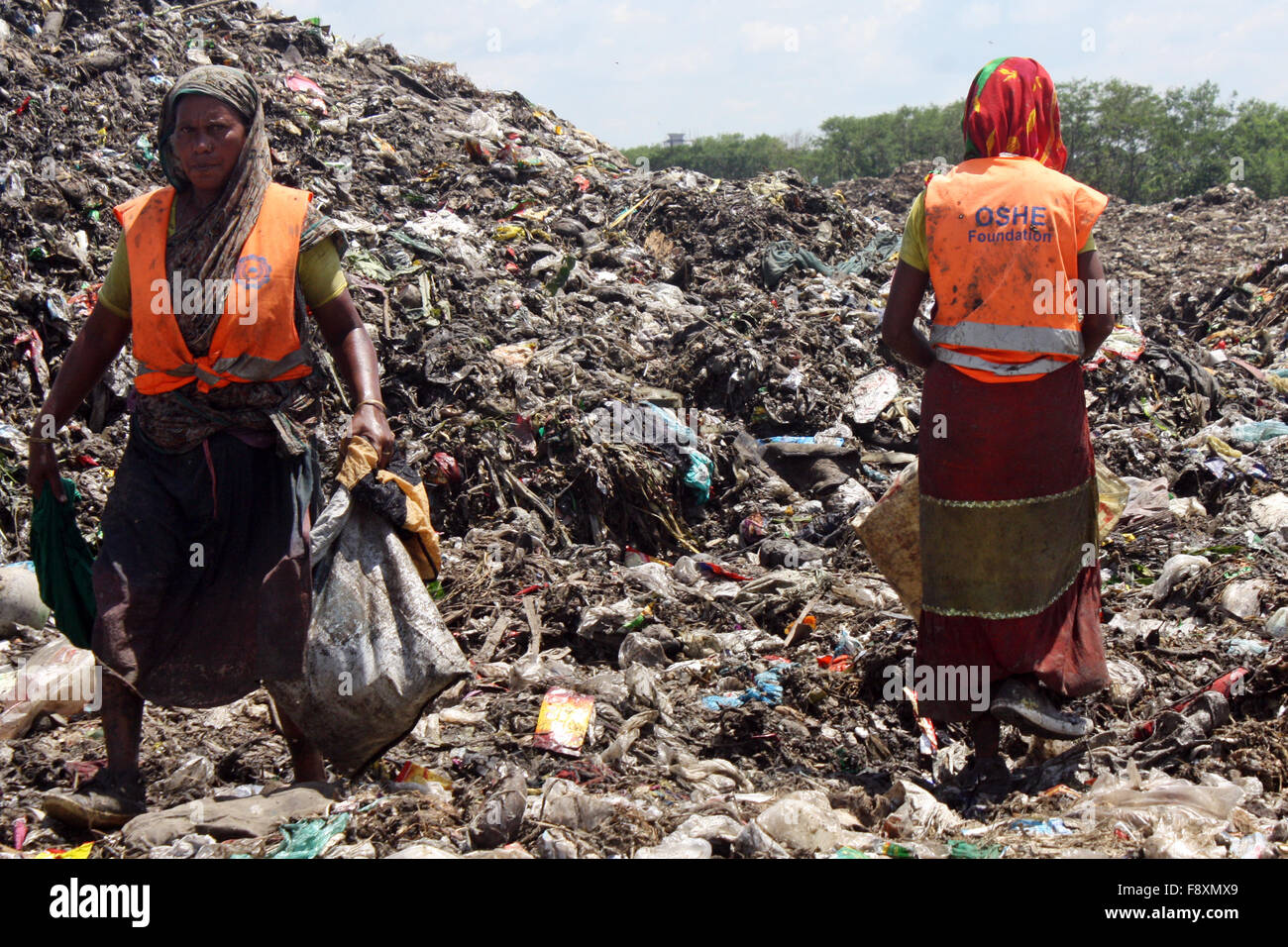 Male and Female waste pickers pick the non- biodegradable waste to be used for the recycling industry in waste Dump - Stock Image