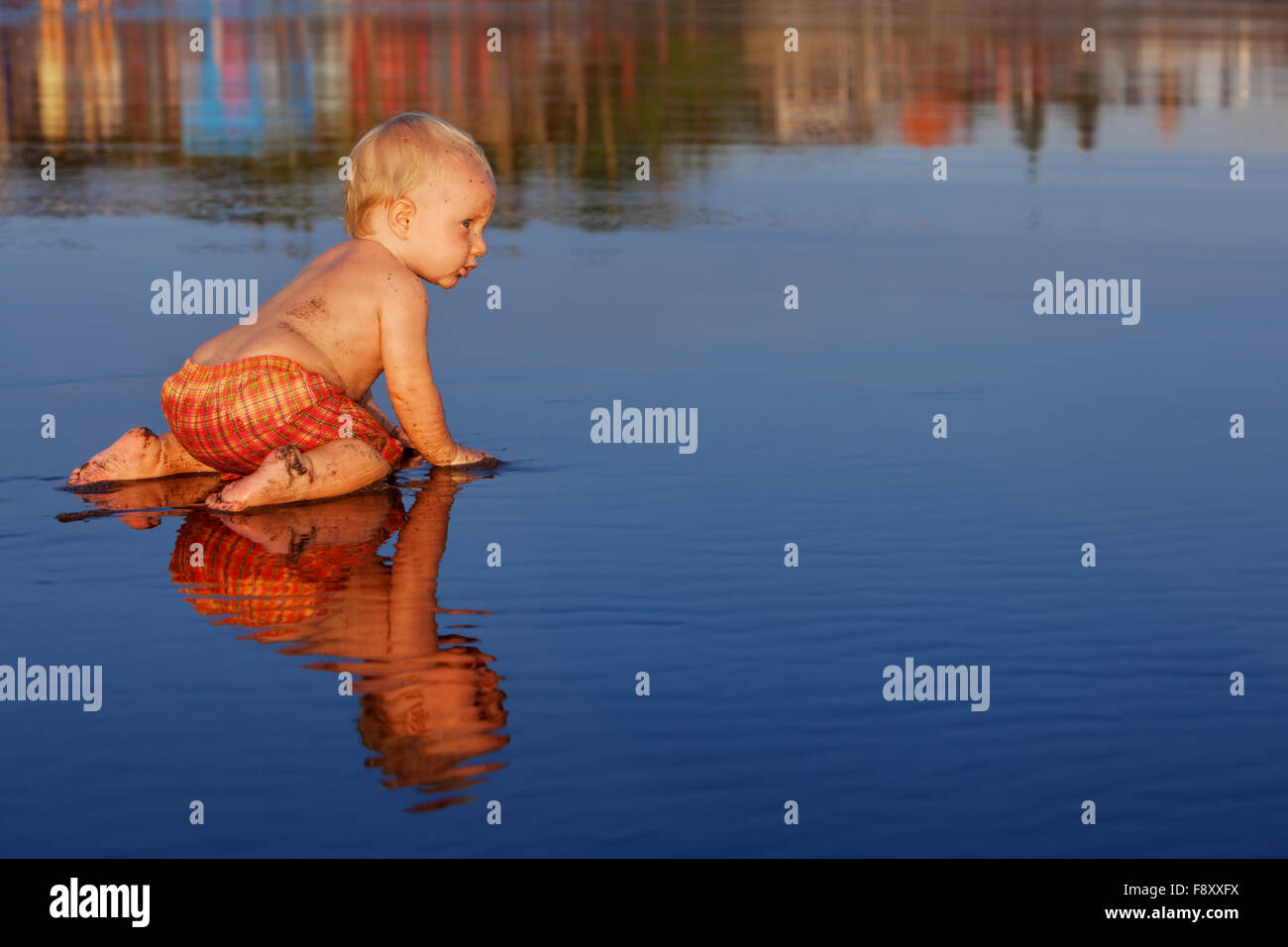 On sunset beach funny baby boy crawling on smoth black wet sand to sea surf for swimming in waves. - Stock Image