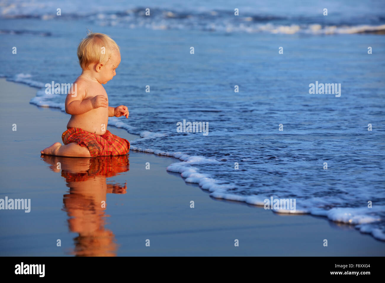 On sunset beach funny baby sit on black wet sand and crawling to sea surf for swimming in waves. - Stock Image