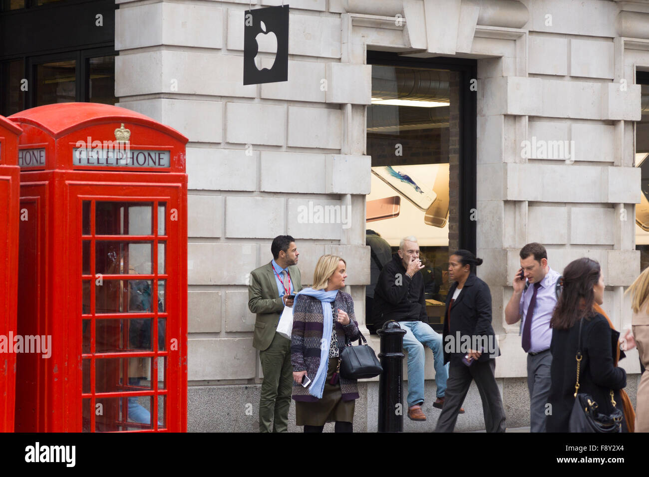 A man sitting smoking and a man eating lunch outside an Apple Store, passed by people at lunch time in London - Stock Image