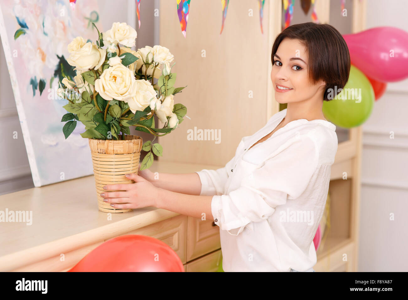 Young girl decorating her apartment for birthday party - Stock Image