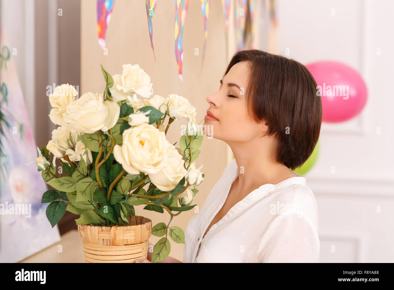 Young lady is smelling the flowers Stock Photo