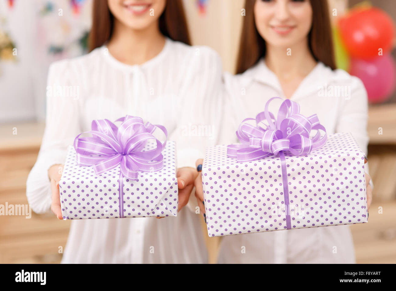 Two young ladies holding presents. - Stock Image