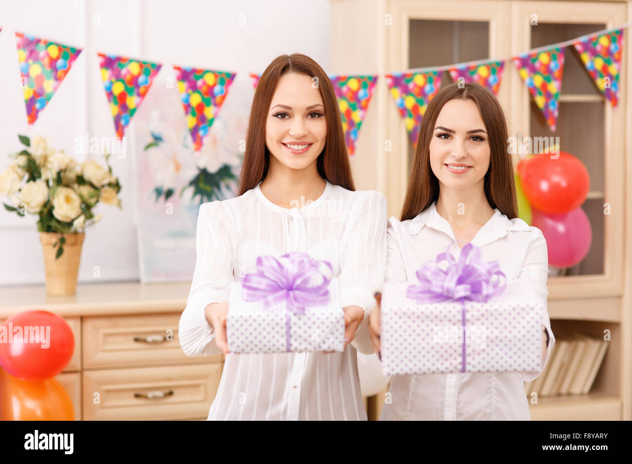 Two young girls are offering presents. - Stock Image