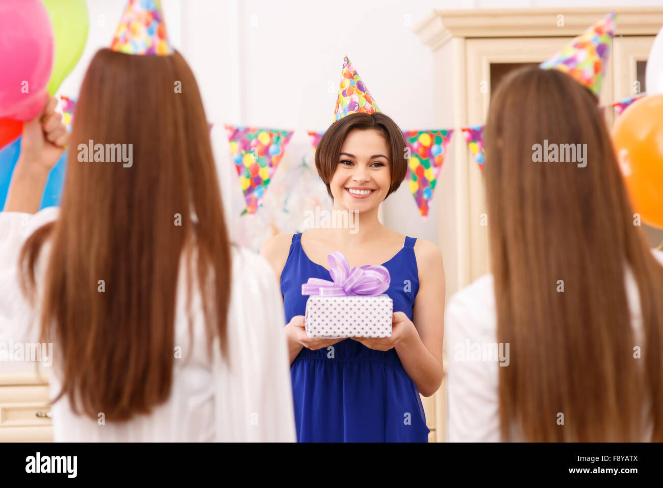 Happy young girl holding a birthday gift - Stock Image