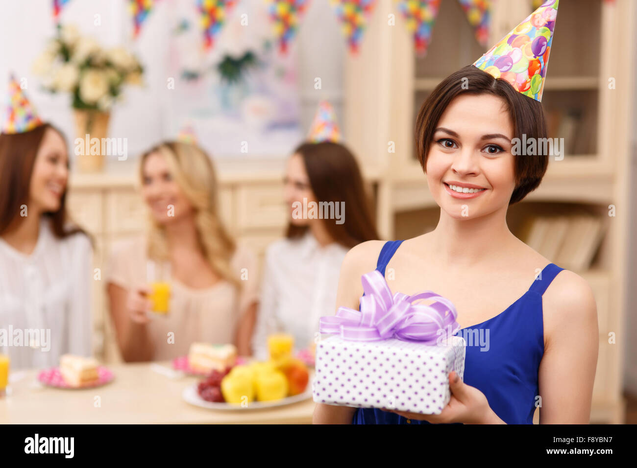 Happy young girl posing with birthday gift - Stock Image
