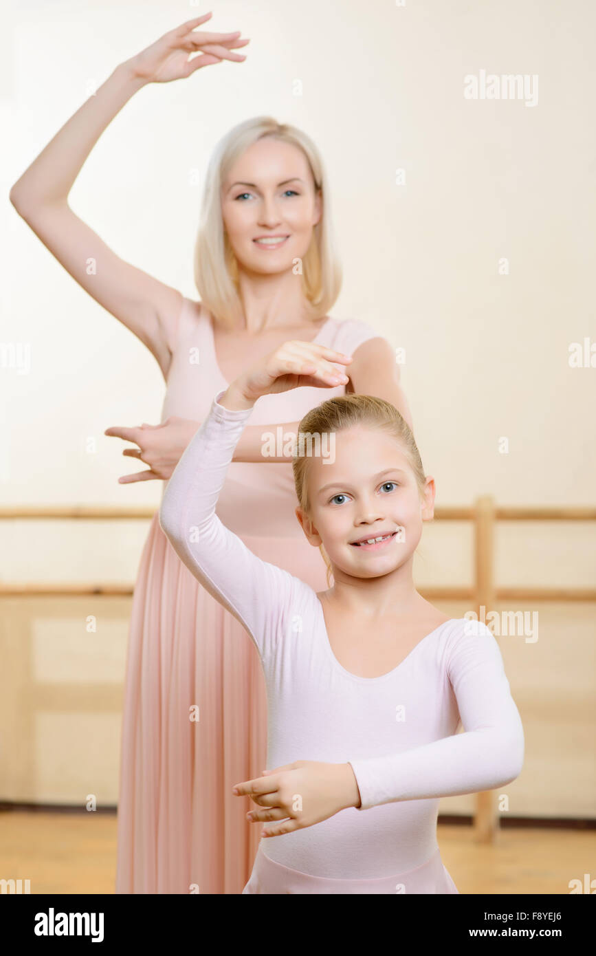 Ballet teacher and her apprentice are holding a pose. - Stock Image