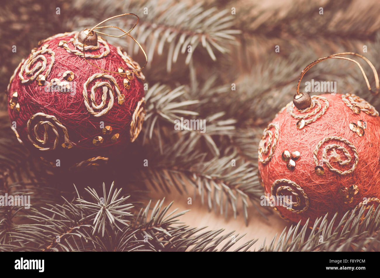 hand made colored christmas decorations on a fir neddles background - retro style - Stock Image