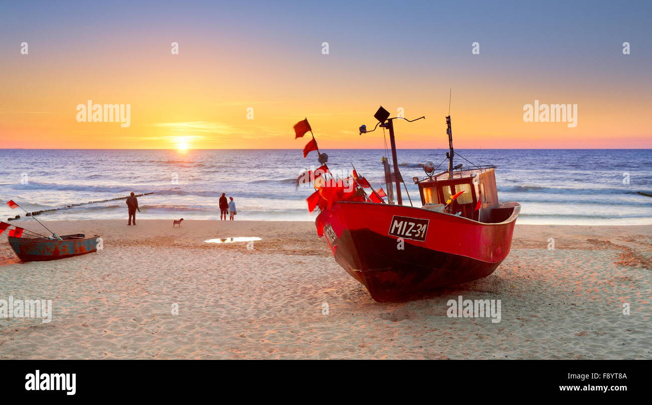 Fishing boat on the beach near the Miedzyzdroje, Baltic Sea at sunset, Poland - Stock Image