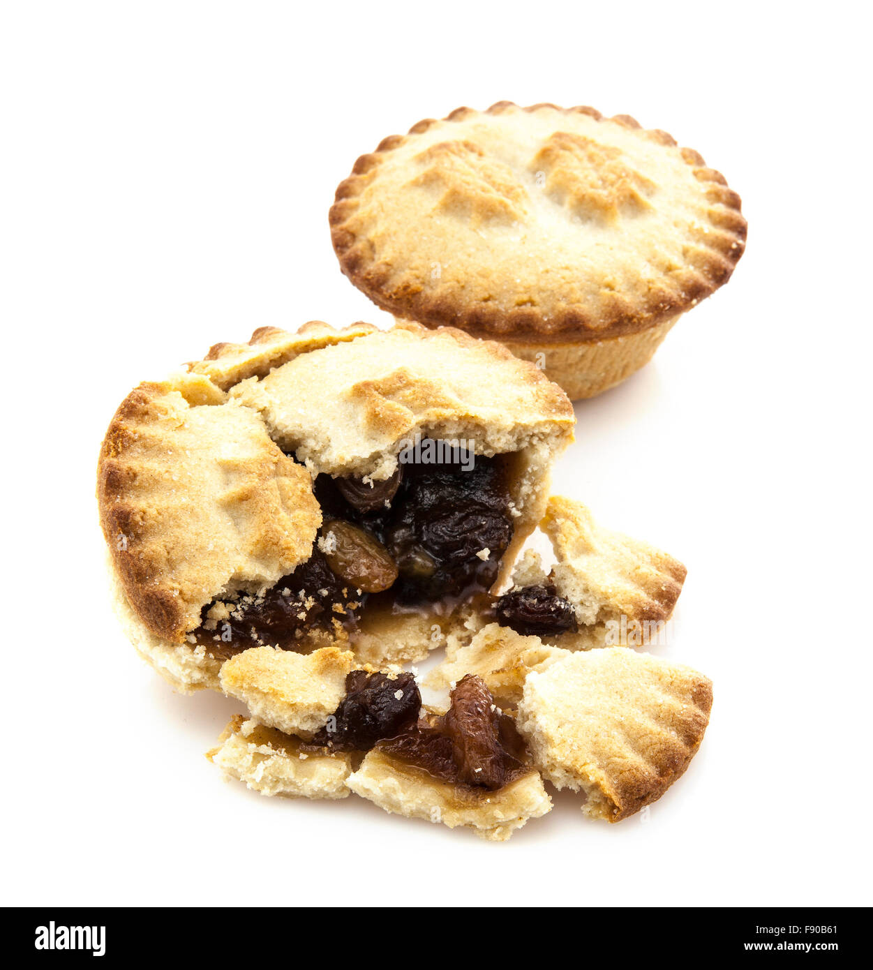 Mince Pie broken in half showing mince on white background - Stock Image