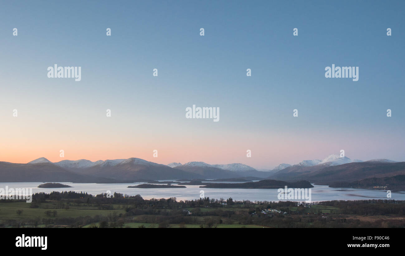 Loch Lomond winter sunset,  with the snow capped peak of Ben Lomond on the right. - Stock Image