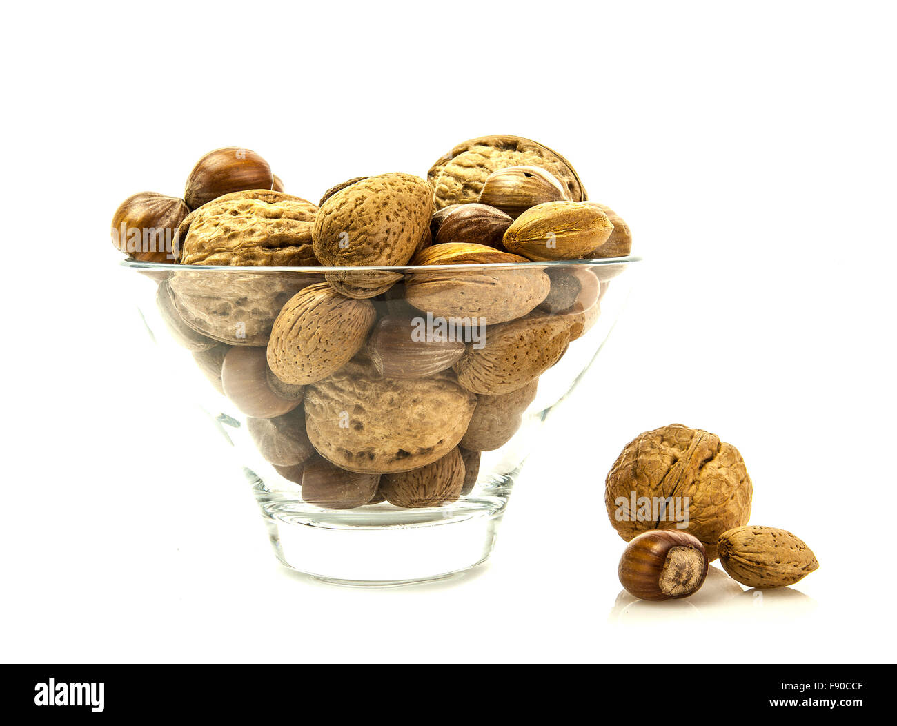 Mixed Nuts in a glass bowl on a white background - Stock Image