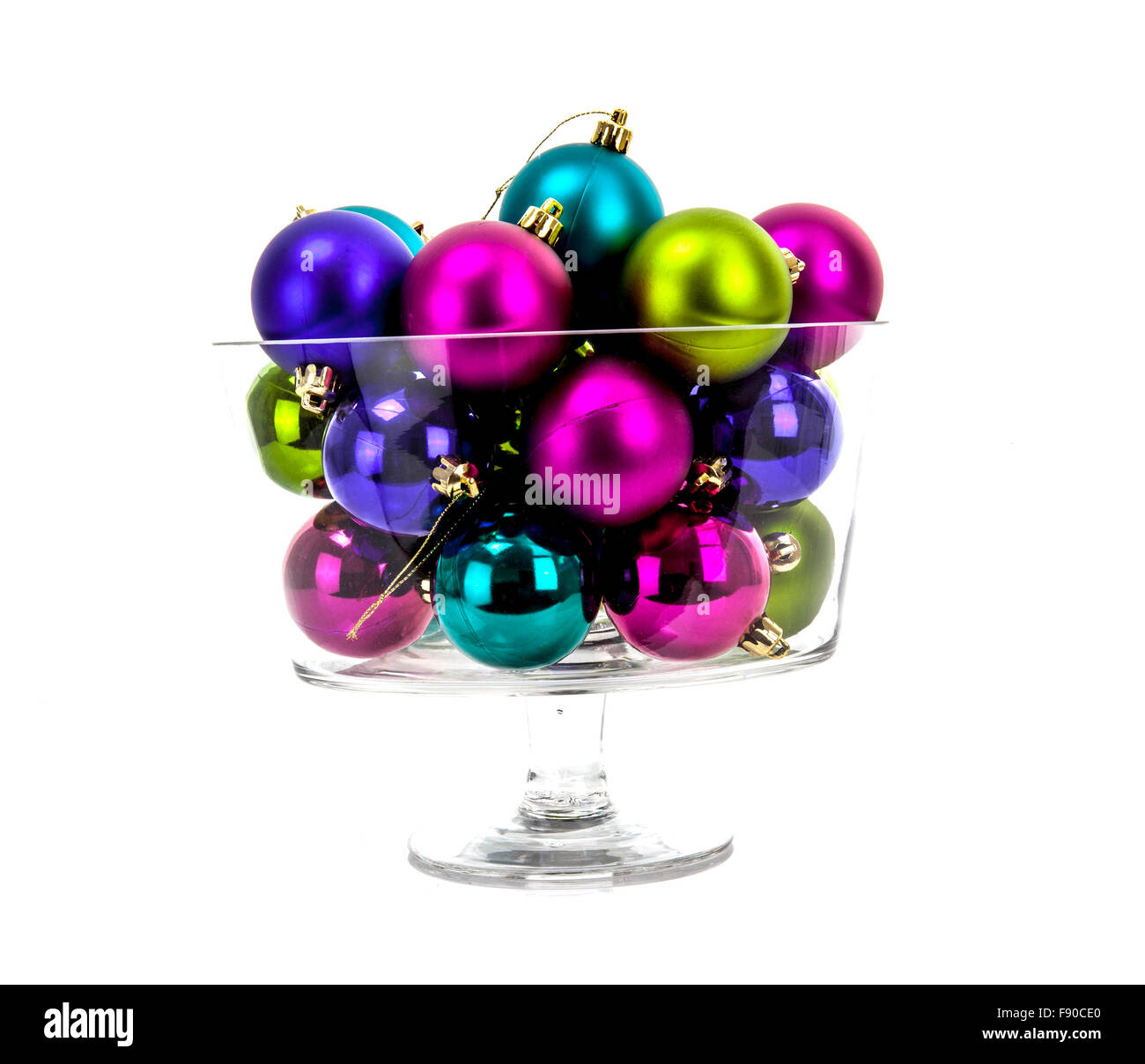 Multi-colored Christmas balls in a glass isolated on a white background - Stock Image