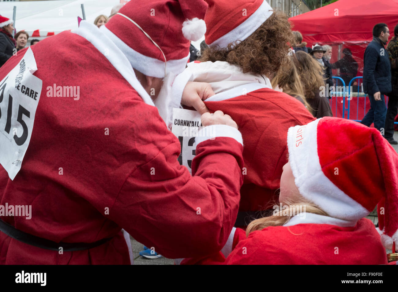 Fun runner pins the race number on his partners back as daughter looks on. Stock Photo