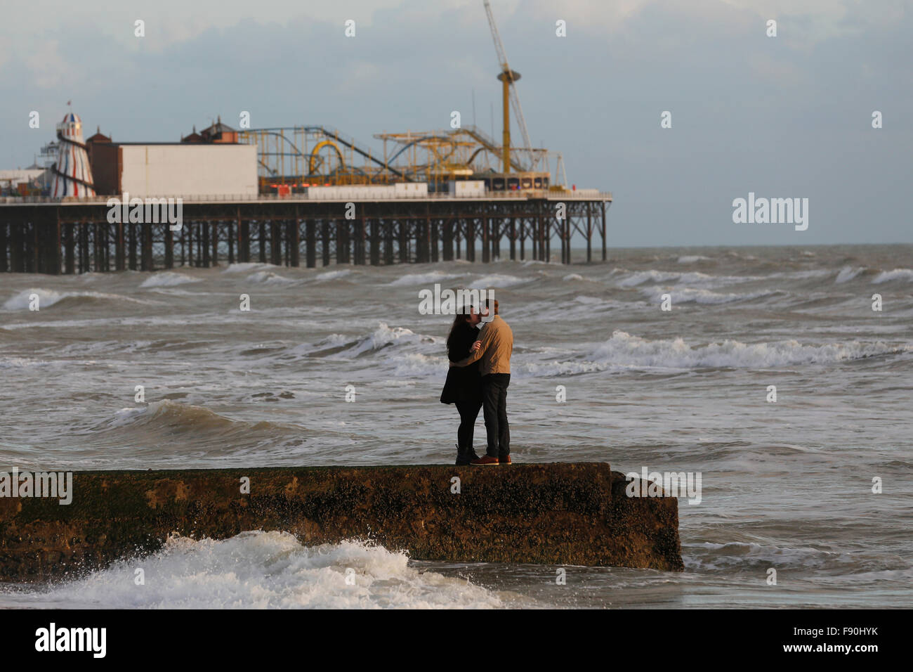 A couple kiss on a jetty in front of Brighton Pier at Brighton, UK Stock Photo