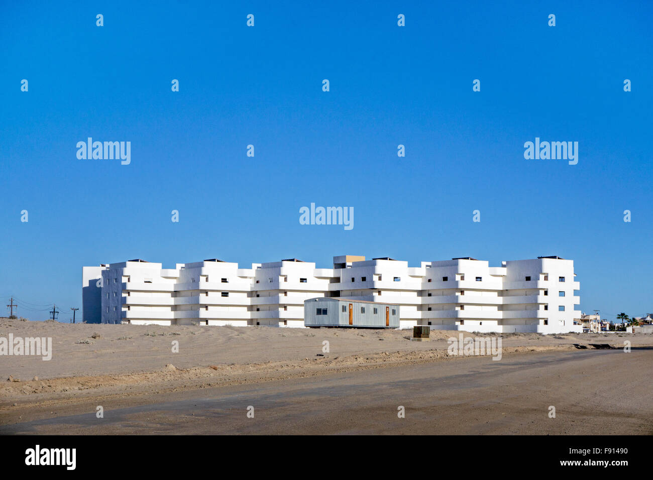 bare white condominium building under construction a block from beach at Playa las Conchas, planned development - Stock Image