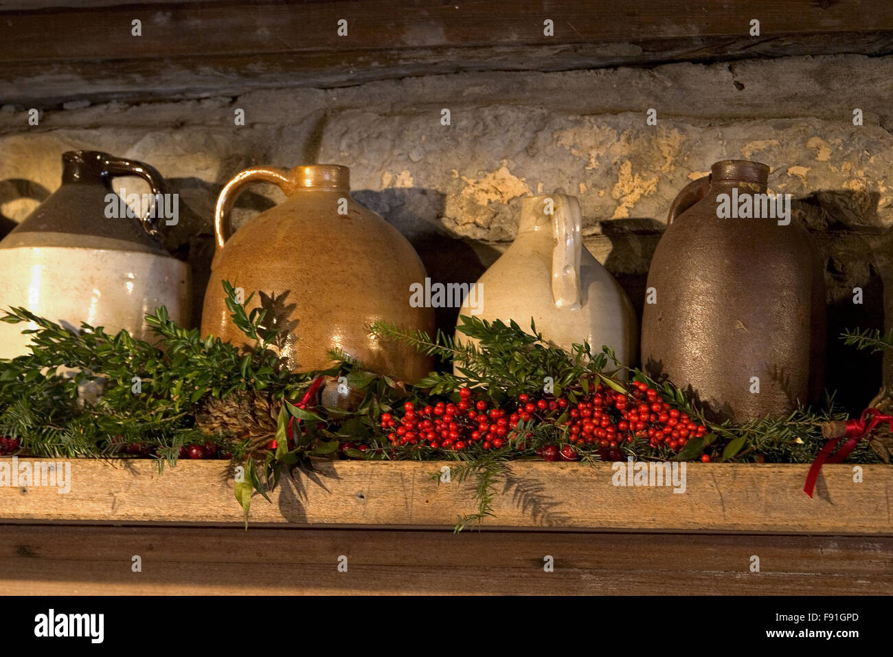 crock jugs on mantel with christmas decorations and berries inside a log cabin at the museum