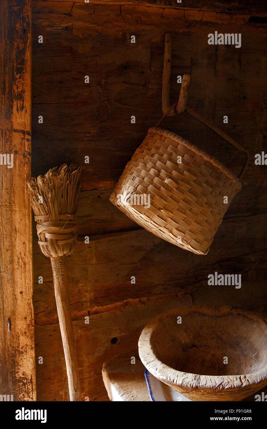 Log cabin interior with a homemade broom, basket, and wooden kneading bowl at the Museum of Appalachia, Tennessee, - Stock Image