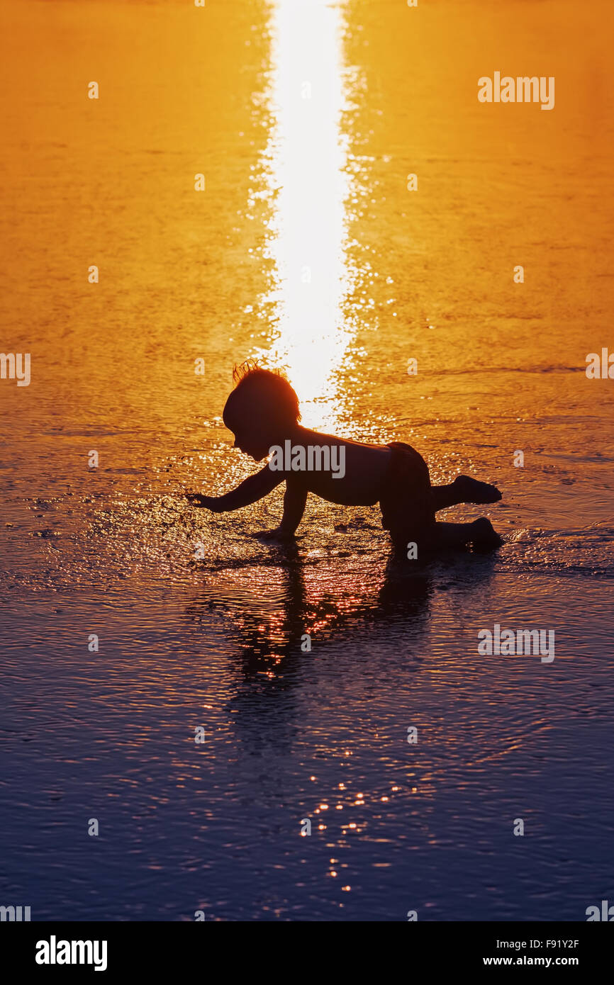 Black shadow silhouette of playful baby running on wet gold sunset sand to sea surf to swim in beach wave. - Stock Image