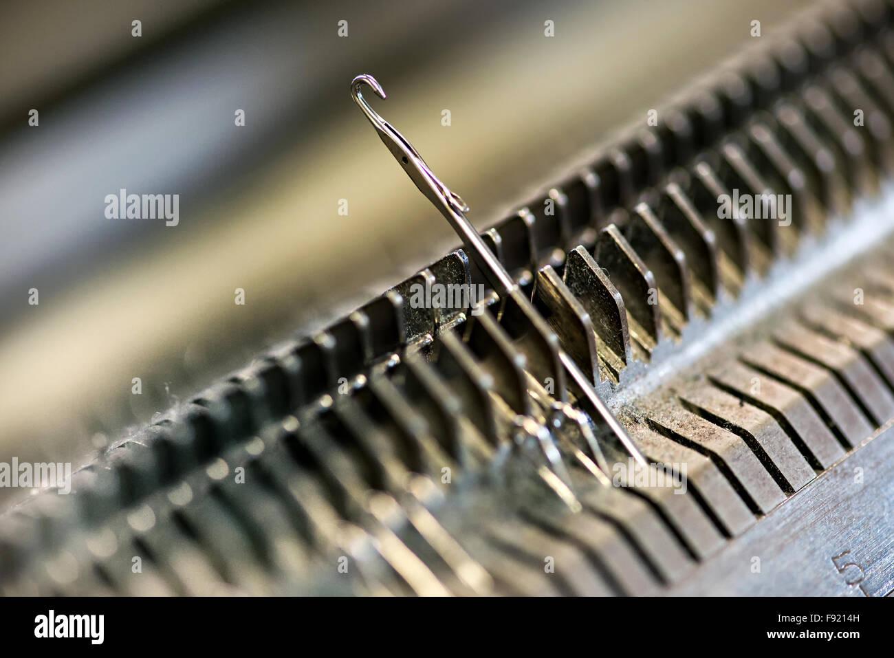 Knitting machine single needle closeup - Stock Image