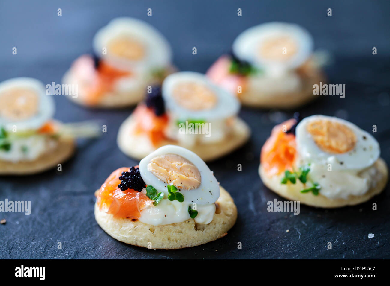 Party food, blinis with salmon, quail egg and caviar Stock Photo