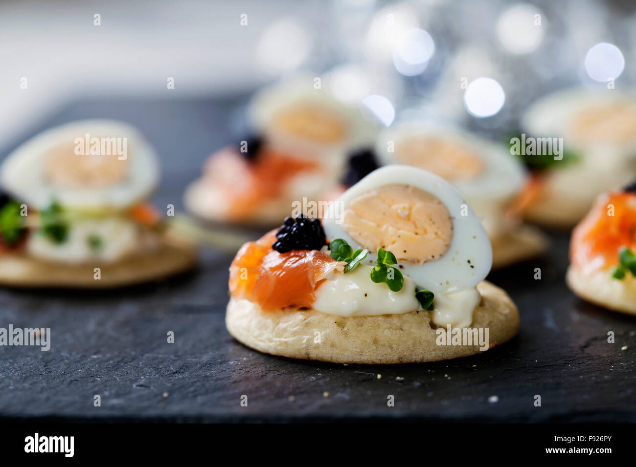 Party food, blinis with salmon, quail egg and caviar - Stock Image