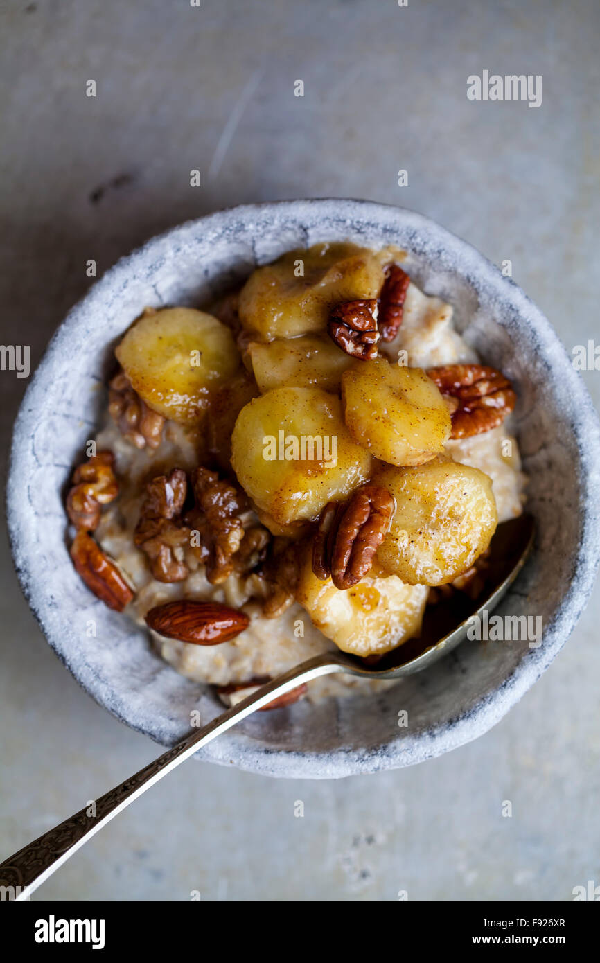 Porridge with caramelized banana and nuts - Stock Image