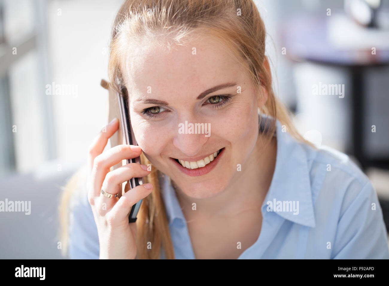 Woman talking on the phone in the cafe - Stock Image